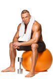 Shaped and healthy body man sitting on fitness Stock Images