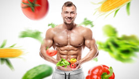 Shaped and healthy bodybuilder holding a fresh vegetables, flyin Stock Photography