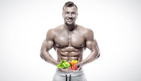 Shaped and healthy bodybuilder holding a fresh vegetables, flyin Royalty Free Stock Images