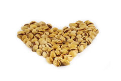 Shaped heart of pistachios. On white background Royalty Free Stock Image