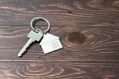 Shaped key ring resting on the wooden floor for the home or rent Stock Photo
