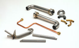 Shaped Metal Tubing. Eleven various shaped brass, copper, stainless steel molded pieces Stock Photos