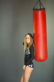 Shapely beautiful girl. Portrait of a slender beautiful young girl in a sport dress next to a punching bag in the gym Stock Photography