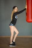Shapely beautiful girl. In sports clothes near a boxing pear in the gym Stock Photo