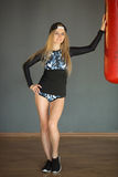 Shapely beautiful girl. In sports clothes near a boxing pear in the gym Stock Photos