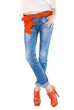 Shapely female legs dressed in blue jeans. Shapely female legs in blue jeans with a scarf as a belt and orange boots with high heels on white background Stock Photo