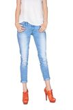Shapely female legs dressed in blue jeans. Shapely female legs dressed in stylish blue jeans and orange boots with high heels on white background Royalty Free Stock Photos