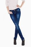 Shapely female legs dressed in dark blue jeans. And black varnished boots on light background Royalty Free Stock Photography