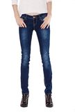 Shapely female legs dressed in dark blue jeans. And black varnished boots on white background Royalty Free Stock Photo