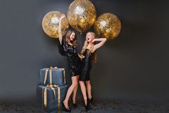Shapely girl with long curly hair fooling around with sister during birthday photoshoot on black background. Enchanting. Ladies in trendy dresses waiting for stock photos