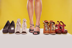 Shapely legs and shoes on display. Shapely sexy female legs wearing sandals in the centre of a shoe display on a yellow studio background Royalty Free Stock Images