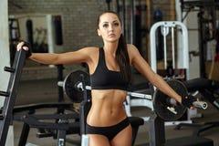 Shapely muscular girl posing in gym Stock Photos