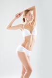 Shapely toned young woman in white lingerie posing with her arms raised, torso view in a fashion, beauty, health, fitness and diet Stock Photos
