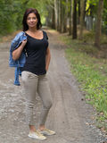 Shapely woman posing. Beautiful middle aged woman posing in a walkway with her short denim jacket Royalty Free Stock Images