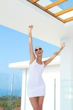 Shapely woman raising her arms in jubilation. Shapely woman in skimpy mini skirt and dark glasses standing on an outdoor summer patio raising her arms in stock photo