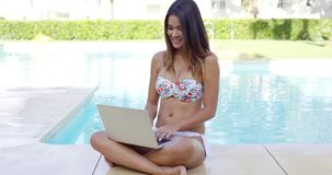 Shapely young woman in a bikini using a laptop stock video footage