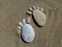 Shapes of feet, pebbles at the sea. Two forms of feet on the sand. They are made with pebbles of the sea on the beach. Sunny day in summer. Nice footsteps royalty free stock photos