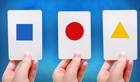 Shapes flash cards. Hands hold up simple shapes on flash cards royalty free stock images