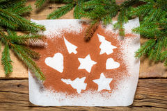Shapes of gingerbread cookies on a sheet of paper and cocoa Stock Photo