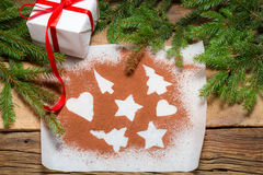 Shapes of gingerbread cookies on a sheet of paper with gift Stock Photography