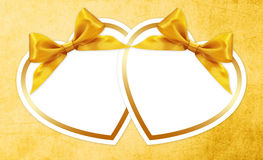 Shapes of hearts with golden ribbon  bow  on yellow Stock Photo