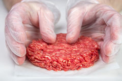 Shaping burger patty. Hand shaping burger patty with disposable vinyl gloves Royalty Free Stock Images