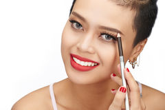 Shaping eyebrows. Very attractive young woman filling eyebrows with pencil Royalty Free Stock Images