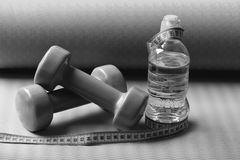 Shaping and fitness equipment. Barbells near cyan measuring tape rol. L and water bottle. Sports and healthy lifestyle concept. Dumbbells made of green plastic royalty free stock photo