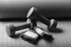 Shaping and fitness equipment. Barbells and pair of hand bands. Lying on yoga mat, close up. Dumbbells made of green plastic on purple and green texture stock image