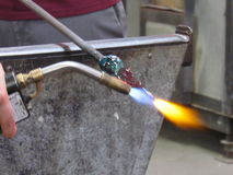 Shaping molten glass. Blue colored glass being shaped with blow torch.   White and yellow flame highlighted by streaked greay metal background of  work bench Stock Images