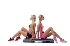 Shaping. Pretty blondes posing sitting on stepper Stock Photo