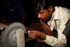 Shaping semi-precious stone for inlay to marble Royalty Free Stock Image