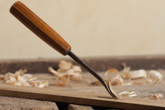 Shaping wood with a chisel. Chisel and wood shavings on a wooden workbench stock photo