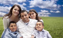 Shappy Hispanic Family Portrait Sitting in Grass Field Royalty Free Stock Photo