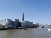 View of The Shard & City Hall along River Thames. View of south bank of the river Thames including City Hall and the Shard with clear blue sky Royalty Free Stock Image