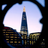 The Shard at dusk. Framed using ironwork on Tower Bridge. This image of the Shard Skyscraper was taken from Tower Bridge over the River Thames in London. The Royalty Free Stock Images