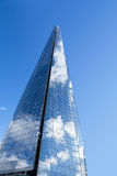 The Shard. In London on its own against a blue sky. Clouds are reflected in the glass panels stock photo