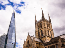 The Shard and Southwark Cathedral in London. Wide view of the modern Shard skyscraper office buidling alongside the 19th-century Southwark Cathedral. London royalty free stock photos
