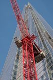 The Shard, tall skyscraper in London UK, on a fine day, viewed from the ground with a red crane in the foreground. Royalty Free Stock Image