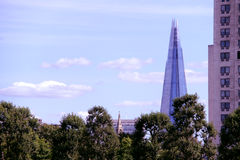 The Shard towering over trees in city. The Shard - Europe's tallest skyscraper as of 2013 in London, England - is seen behind a row of trees in the city Stock Images