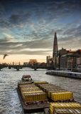 The shard view from millennium bridge. The shard during sunset view from millennium bridge with tug boat and barge passing by at thames river royalty free stock images