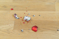 Shards of a broken christmas ball on a wooden floor.  stock image