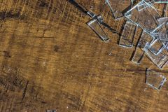 Shards of broken glass. Scattered on wooden floor royalty free stock image