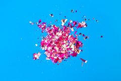 Shards of sequins slim a broken stained glass on a bright blue background,. Abstract festive background stock image