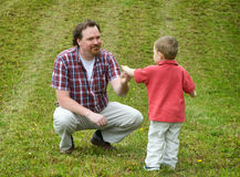 Share Alike. Father and Son interacting outdoors in a grassy field royalty free stock photography