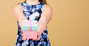 Share and generosity. Thank you so much. Child hold gift box beige background. Kid girl delighted gift. Girl adorable