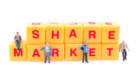 Share market. Small figurine on yellow blocks written share market on them Royalty Free Stock Image