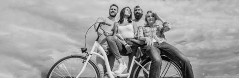 Share or rental bike service. Bicycle as best friend. Company stylish young people spend leisure outdoors sky background. Cycling modernity and national royalty free stock image