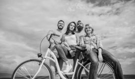Share or rental bike service. Group friends hang out with bicycle. Bicycle as best friend. Company stylish young people. Spend leisure outdoors sky background royalty free stock image