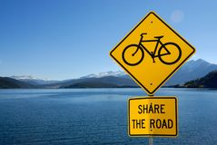 Share the road. Sign by the lake Stock Photo